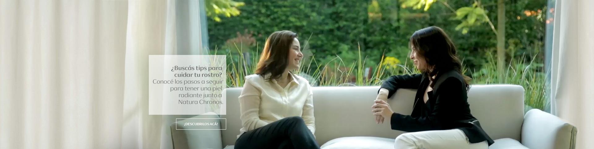 dos mujeres conversando, sentadas en un sillón blanco y detrás una ventana con vegetación
