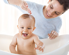 Mamá bañando a su bebé en una bañera