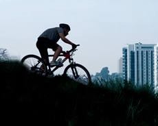 Hombre conduciendo una bicicleta sobre un pastizal, de fondo aparece un edificio