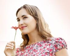 mujer sintiendo el aroma de una rosa