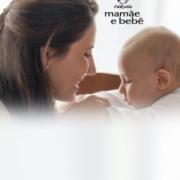 Mama con su bebe en la cuna, bebe tocando la boca de la mama sonriendo