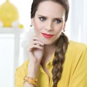 Mujer maquillada en ojos y labios con productos Natura Aquarela, sonriendo