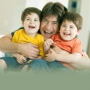 Padre con sus dos hijos abrazados y sonriendo