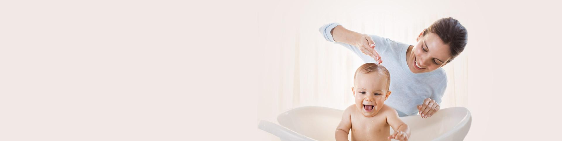 Mamá bañando a su bebé en la bañera